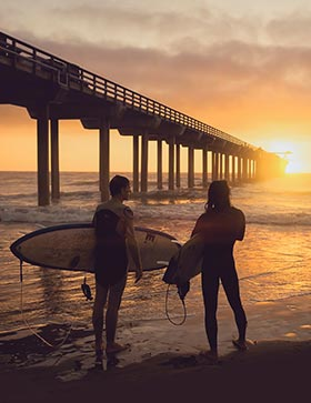 Surfers in California sunset